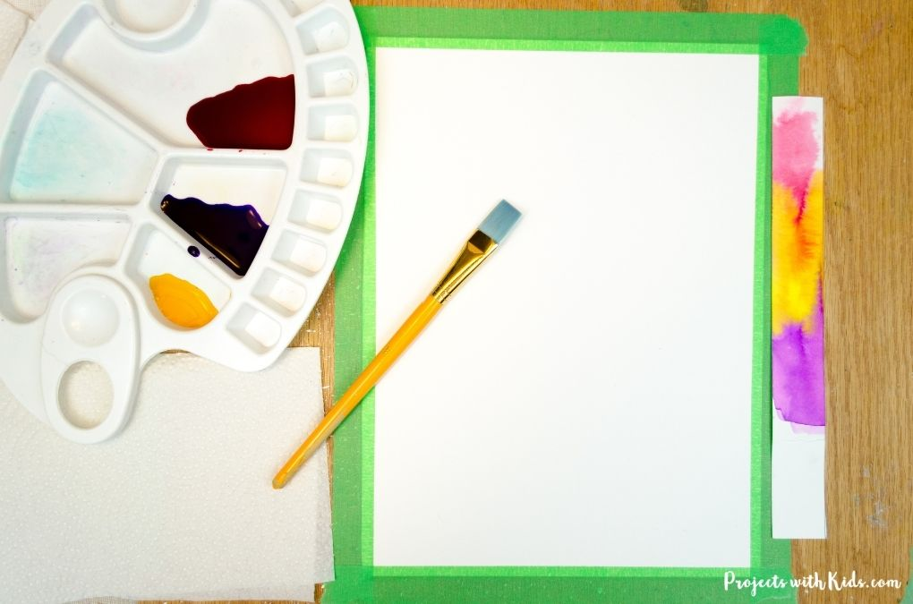 Taping waterclor paper down to a wooden board and mixing liquid watercolor paint in a palette