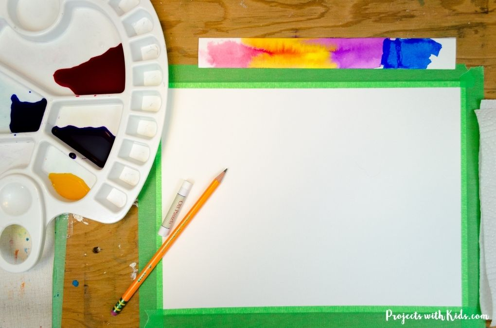 Watercolor paper taped down to a wooden board and liquid watercolors in paint palette.