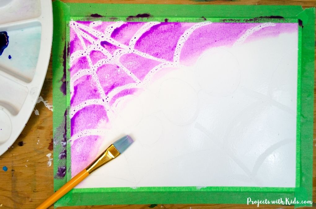 Painting a Halloween art proejct with purple liquid watercolors.