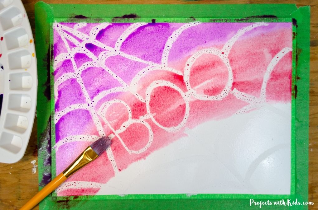 Painting a spider web with watercolors using a oil pastel resist technique.