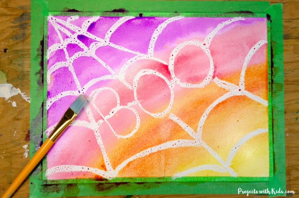 Watercolor resist painting of a spider web with the word boo in it