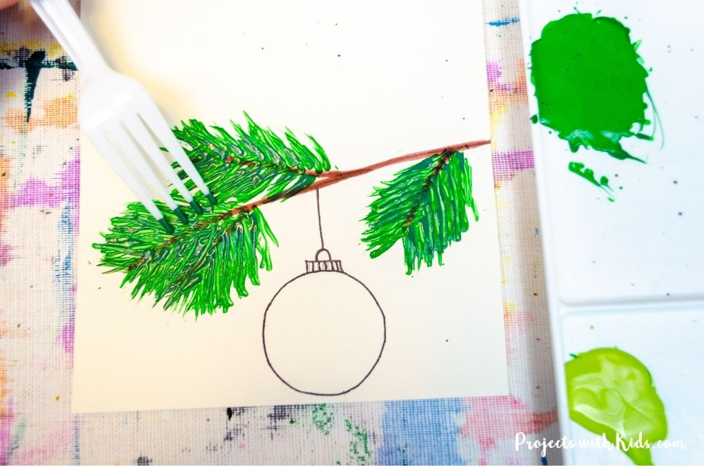 Painting a tree branch with a fork and green acrylic paint.