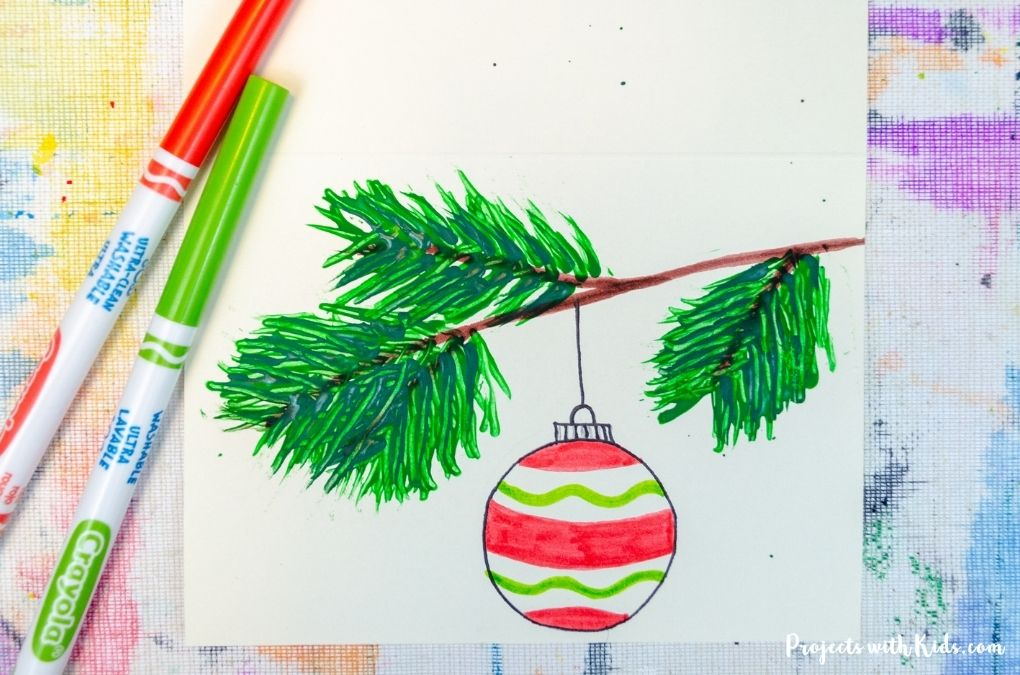 Fork painted tree branch with Christmas ornament hanging down