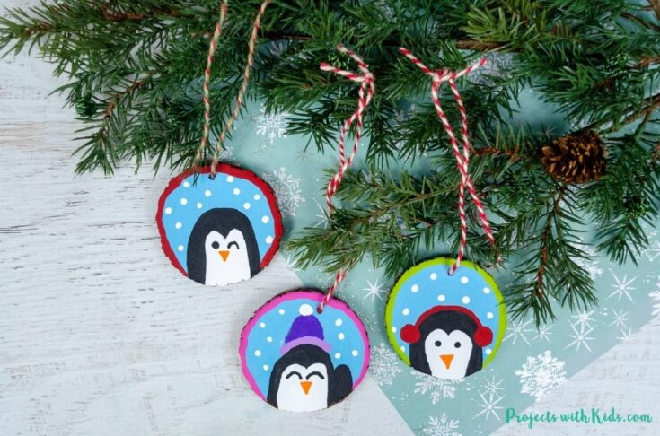 DIY penguin ornaments using wood slices and acrylic paint.