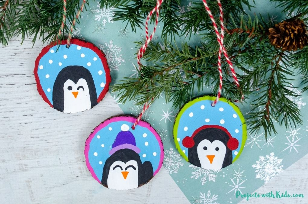 DIY penguin ornaments using wood slices and acrylic paint