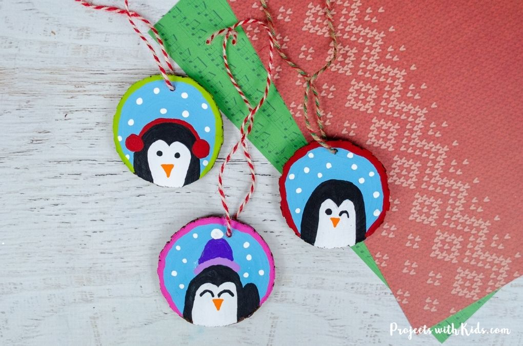 Wood slice DIY penguin ornaments for kids to make Christmas craft.