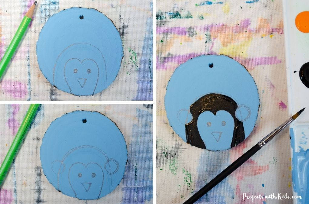 Drawing a penguin on a wood slice Christmas ornament.