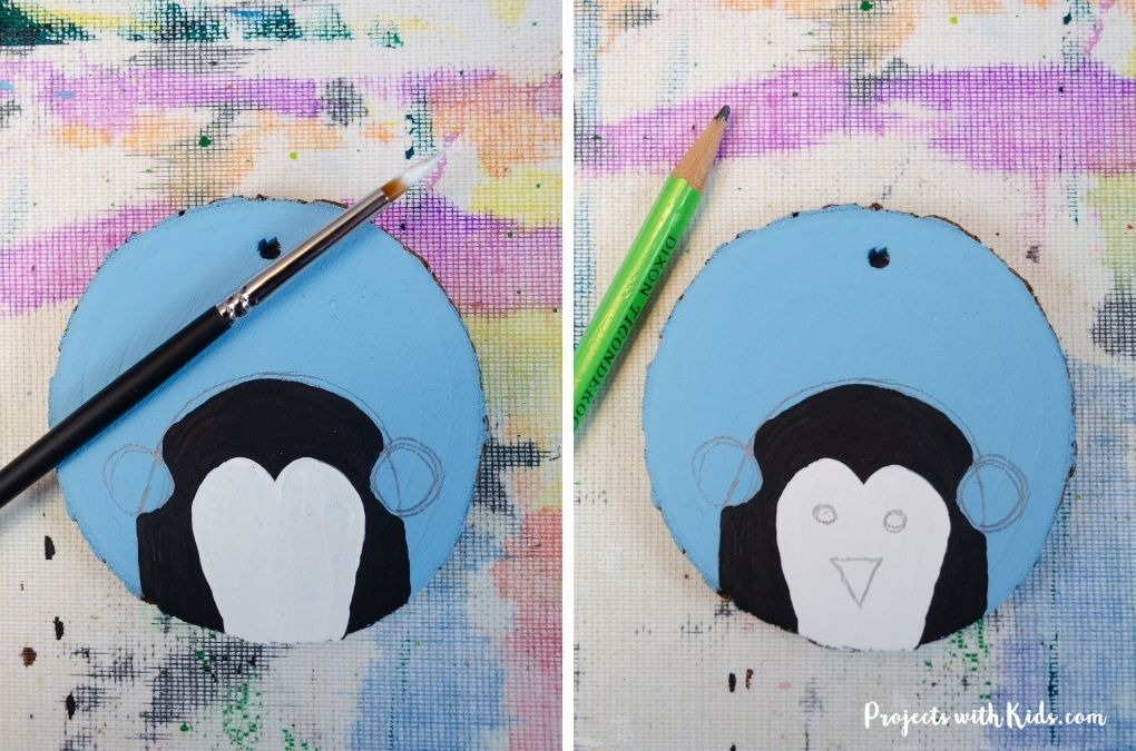 Painting a wood slice ornament with acrylic paint.