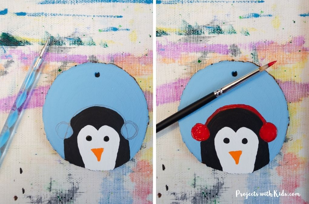 Painting a penguin on a wood slice ornament.