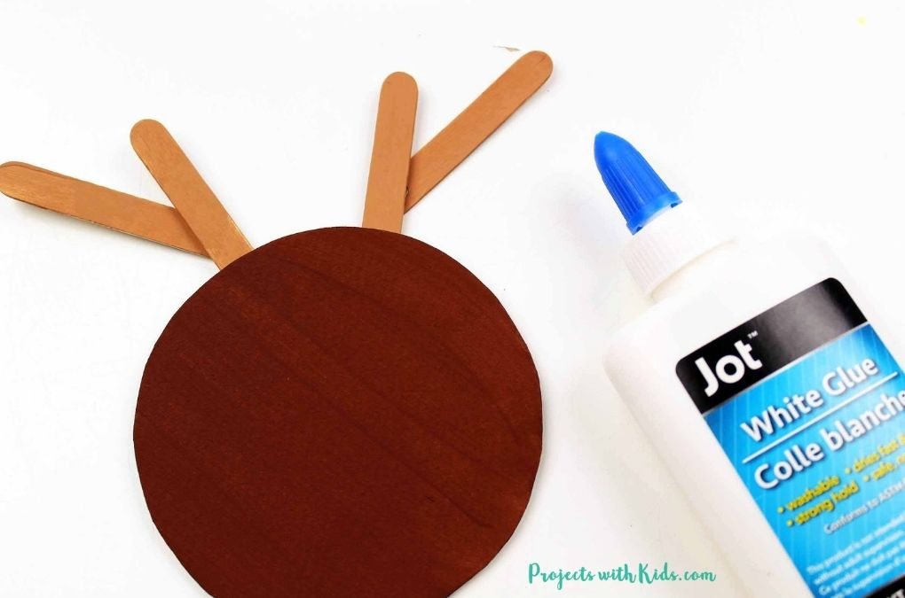 Using white glue to glue popsicle stick antlers to a reindeer craft.