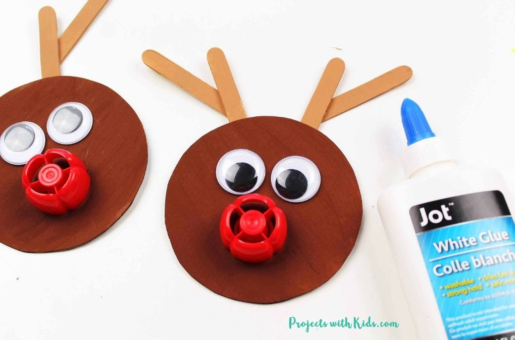 Glueing nose and eyes onto a reindeer ornament craft