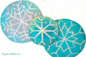 DIY snowflake ornaments using watercolors and oil pastels for kids to make