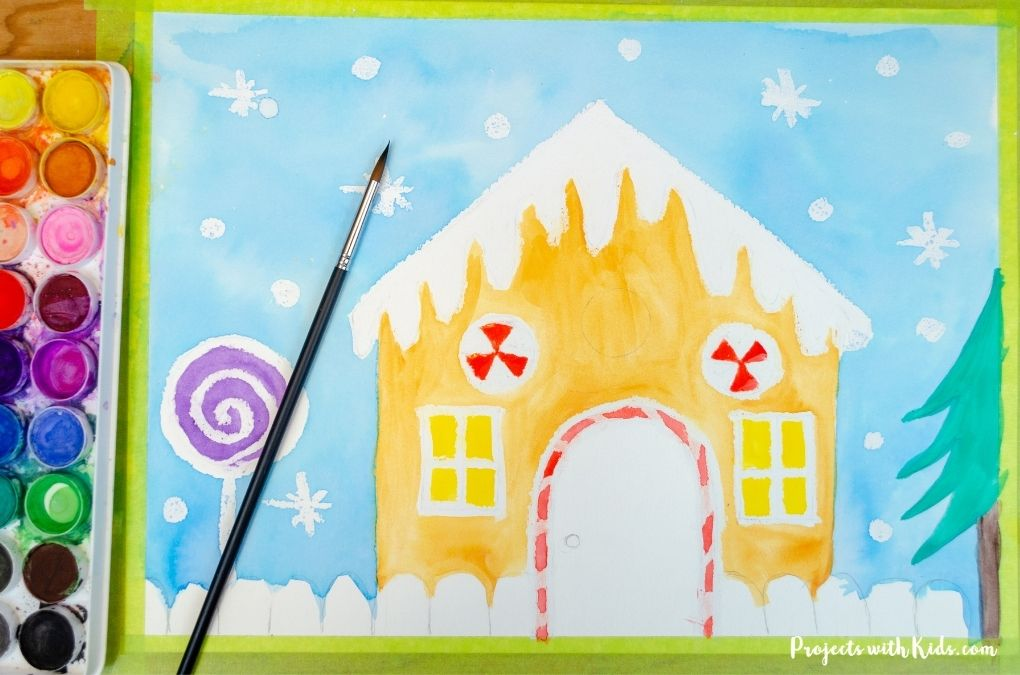 Painting a gingerbread house with watercolors.