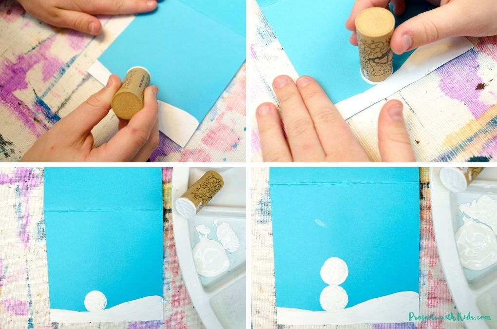 Using a cork to paint a snowman onto blue cardstcok