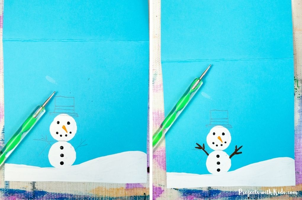Using a dotting tool to paint on snowman details.