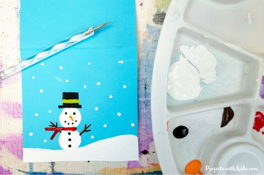 Use a dotting tool to paint on snow to blue cardstock.