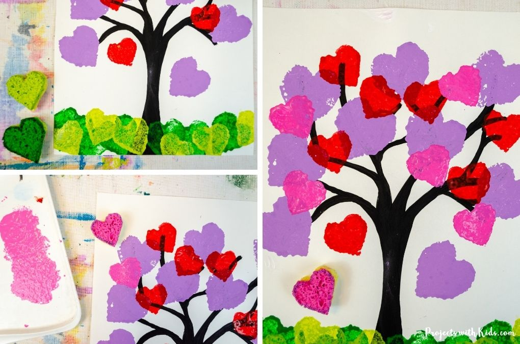 Painting on paper with green and pink heart sponges.