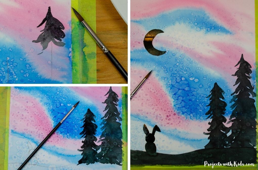 Painting evergreen trees, a rabbit and crescent moon with black watercolor.