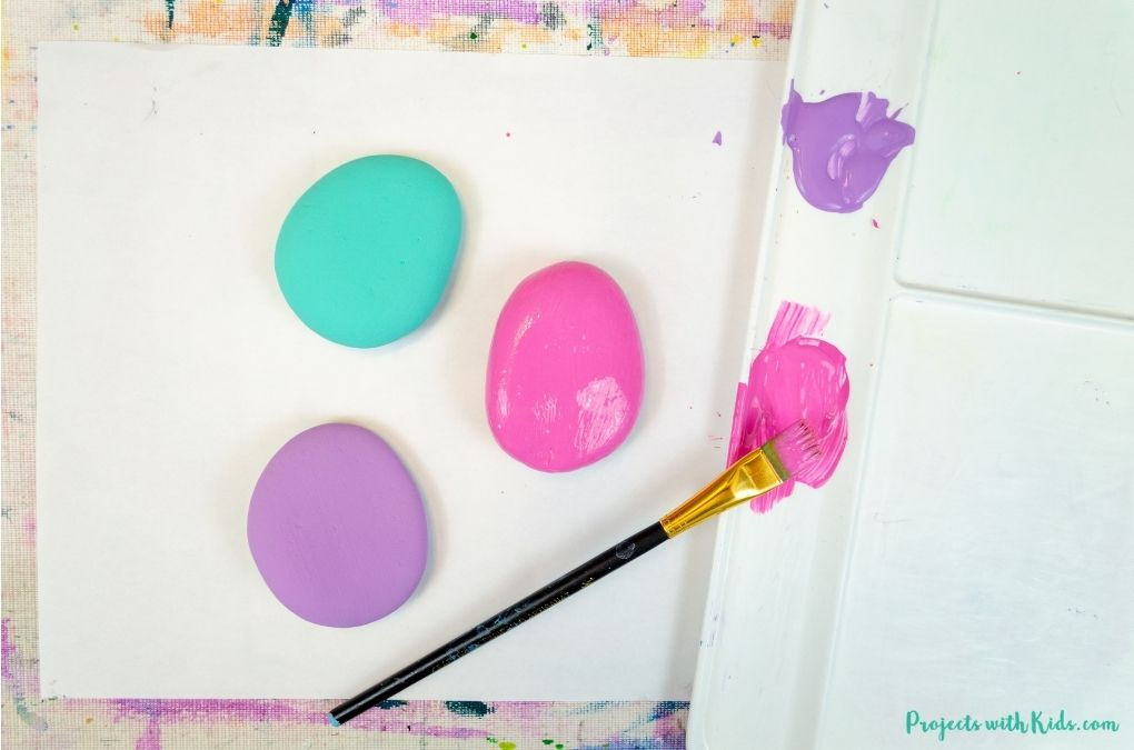 Painting rocks with blue, purple and pink acrylic paint.