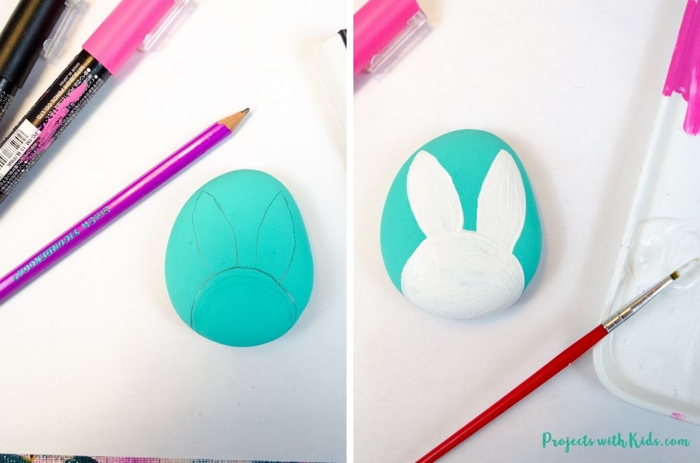Drawing and painting a bunny face on a blue painted rock.
