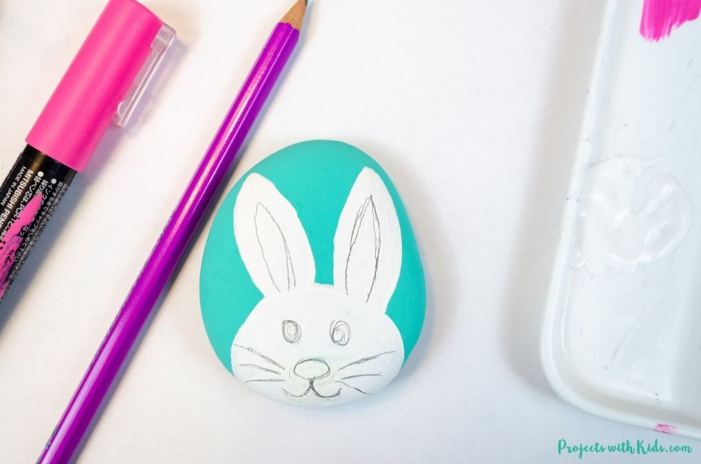 Drawing a bunny face on a painted rock.