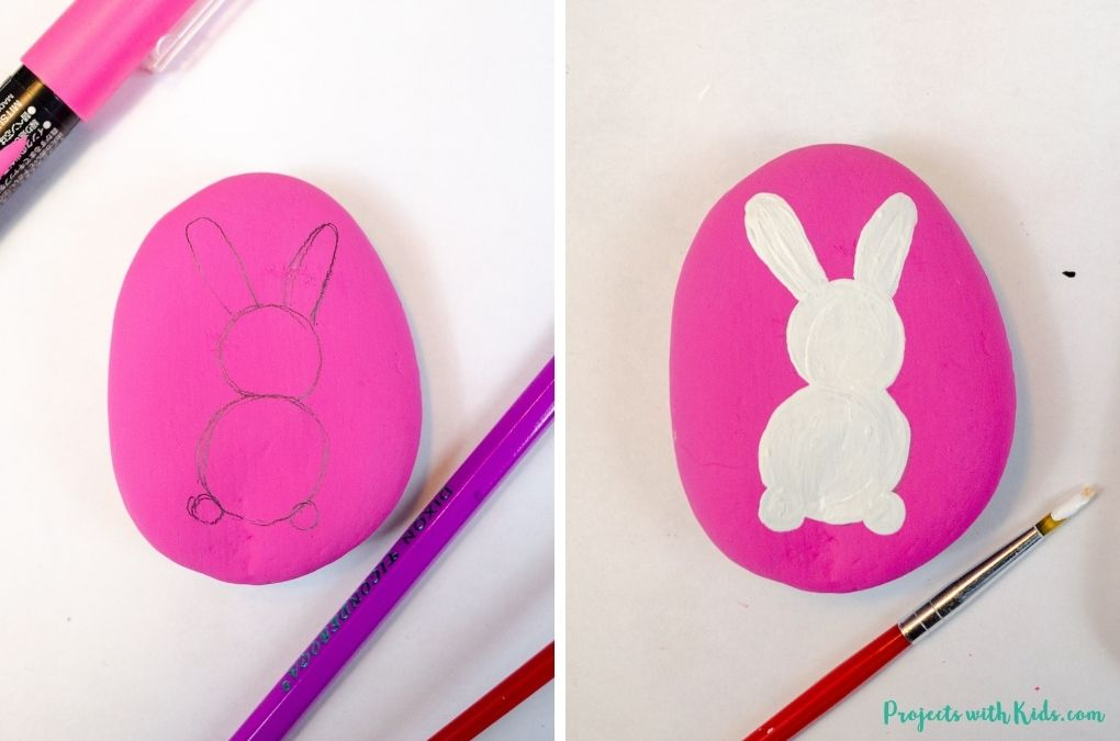 Drawing and painted a bunny with white acrylic paint on a pink painted rock.