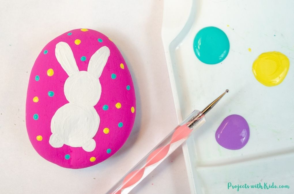 Using a dotting tool to paint dots on a rock