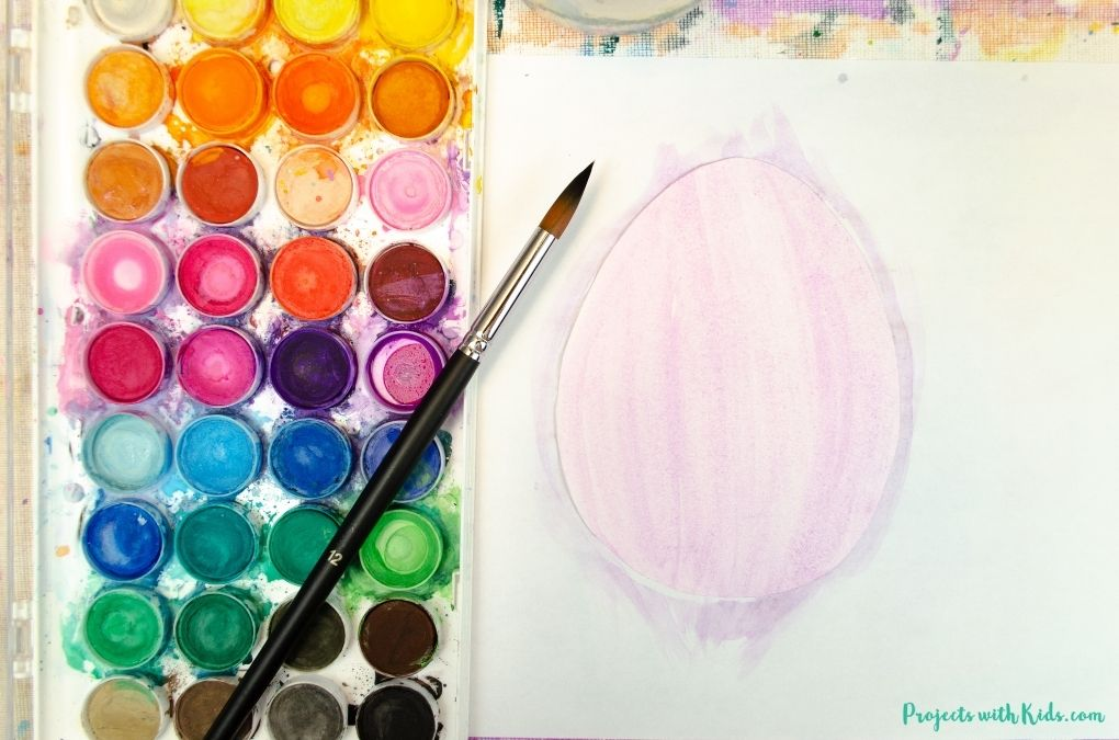 Painting a paper Easter egg template with purple watercolor paint.