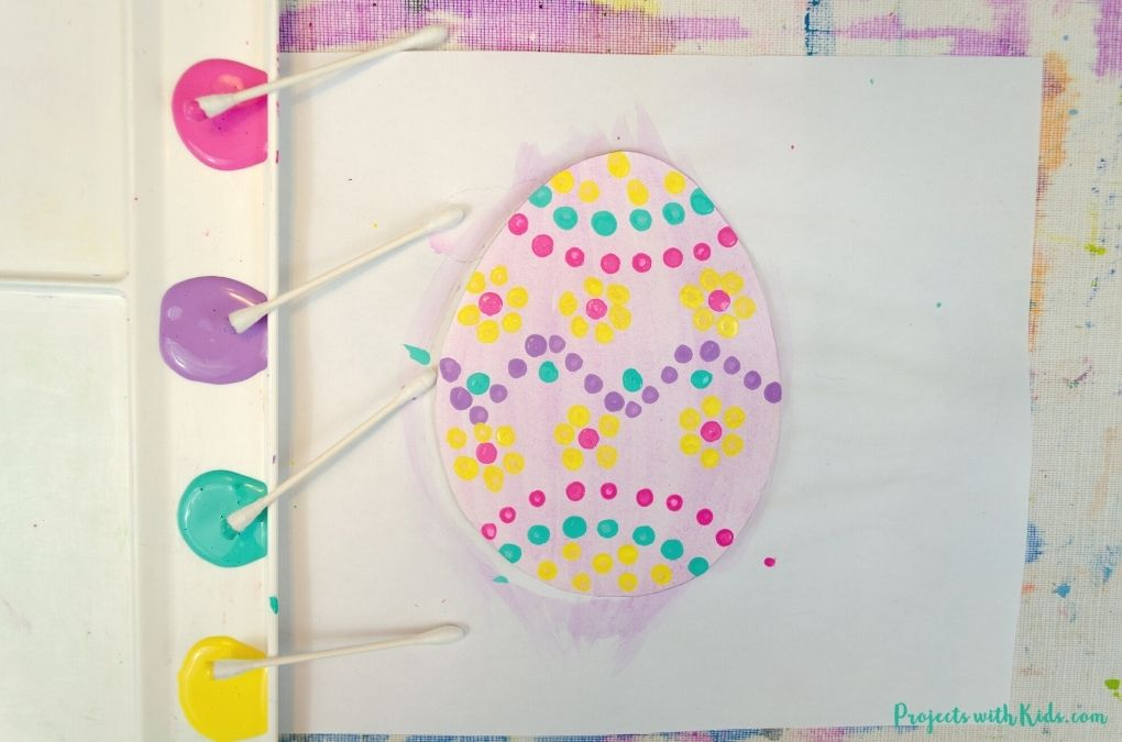 Painting a design on a paper Easter egg with paint and q-tips.