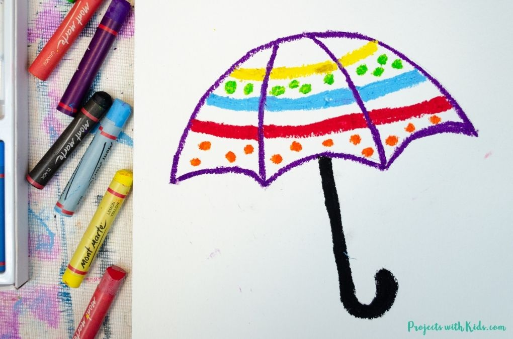Using oil pastels to decorate an umbrella on watercolor paper.