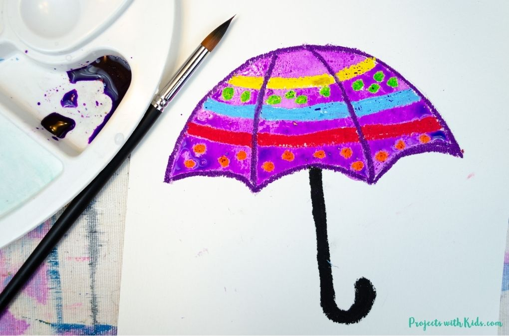 Using watercolors and oil pastels for an umbrella painting