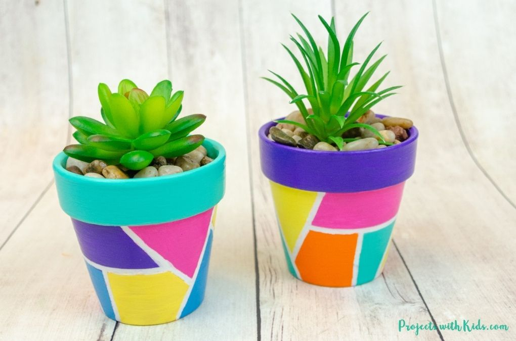 painted flower pots with geometric design for spring or summer kids craft idea.