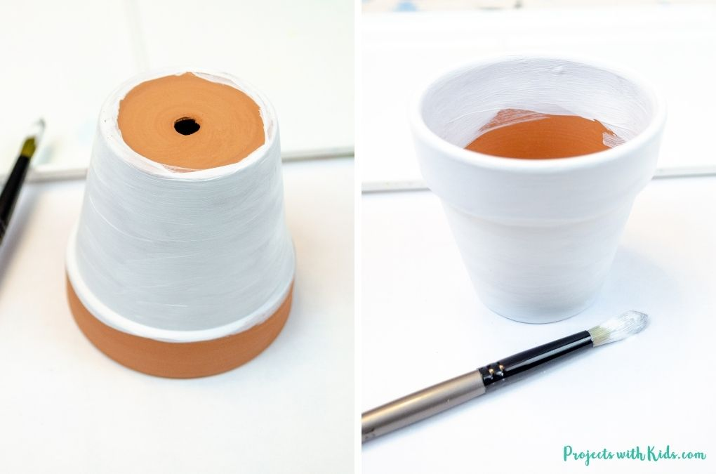 Painting a mini flower pot with white acrylic paint.