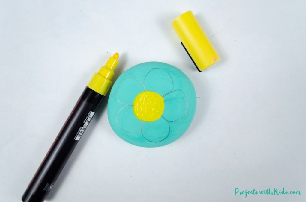 Coloring in the centre of a flower with a yellow paint pen for a rock painting craft for kids