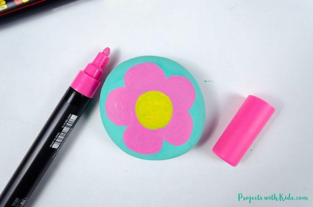 Coloring a flower with pink petals using a paint pen on a rock.