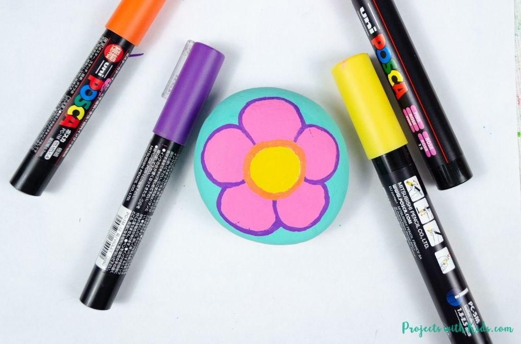 Coloring a purple outline on a flower painted rock with a paint pen.