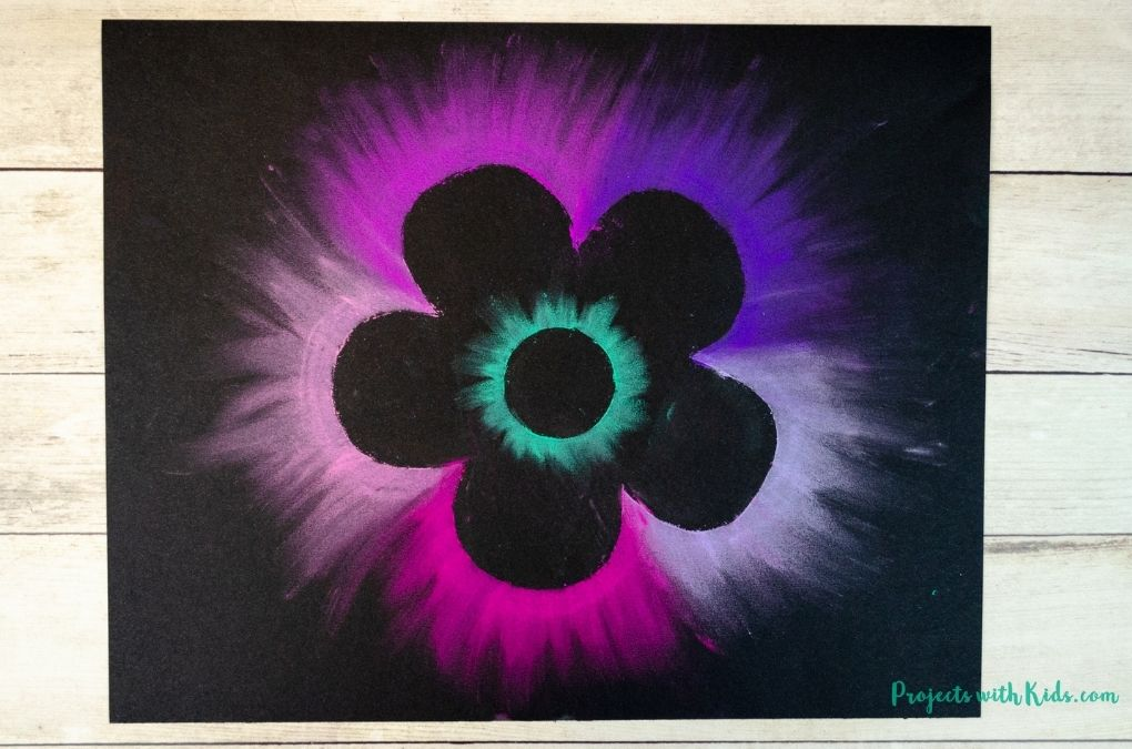 Purple and pink chalk pastel flower on black drawing paper