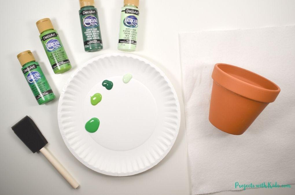 Green acrylic paint and mini terra cotta pot