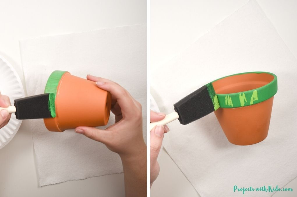 Painting green on a flower pot for a kids craft