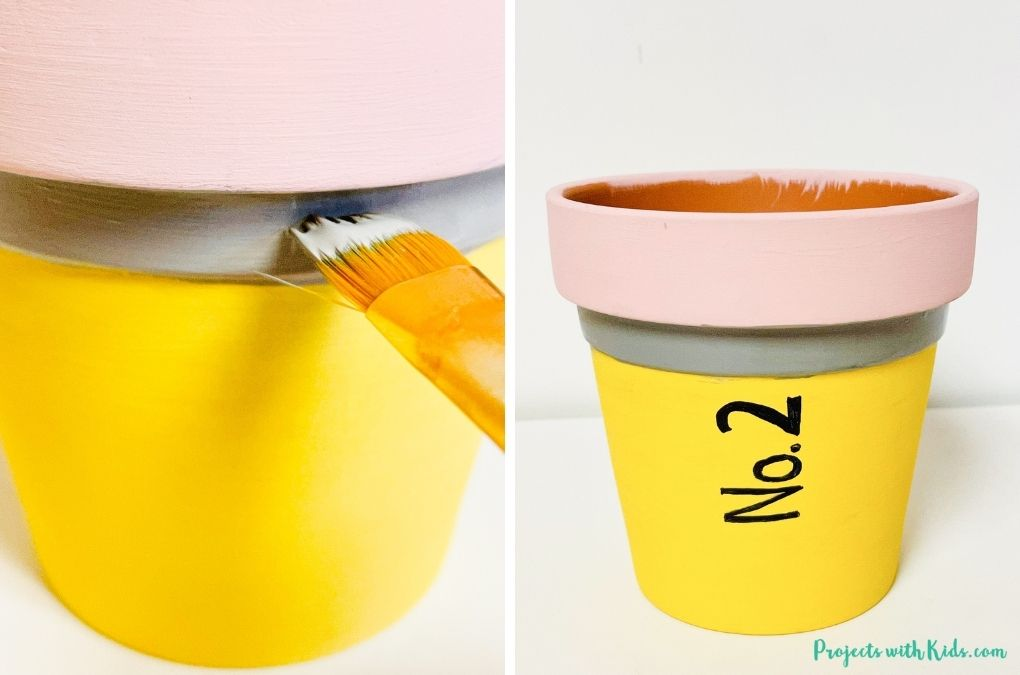 Painting with grey acrylic paint onto a terra cotta pot to make a back to school craft