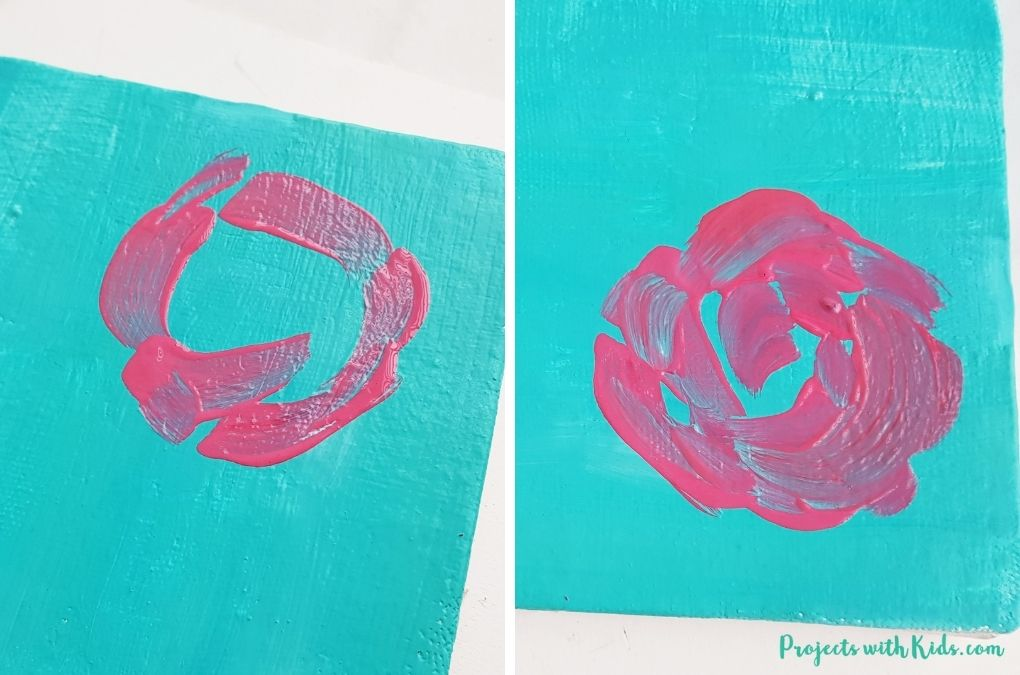 Using pink paint to start a rose painting