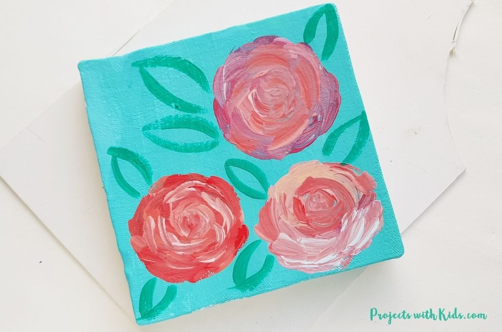 Adding in leaf shapes to a rose painting on canvas art project for kids