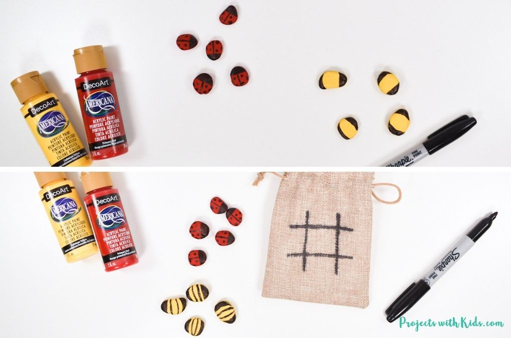 Using a sharpie to add ladybug and bee details to painted rocks