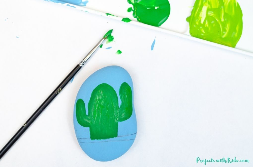 Painting a cactus on a rock with green acrylic paint.