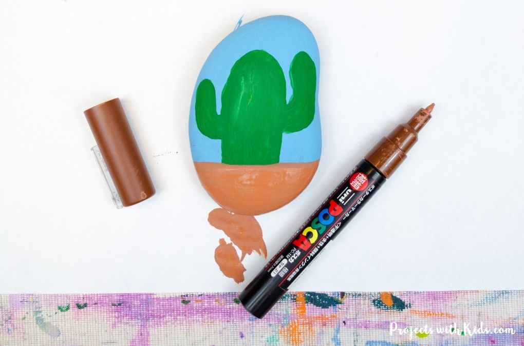 Painting a cactus on a rock with paint pens and acrylic paint.