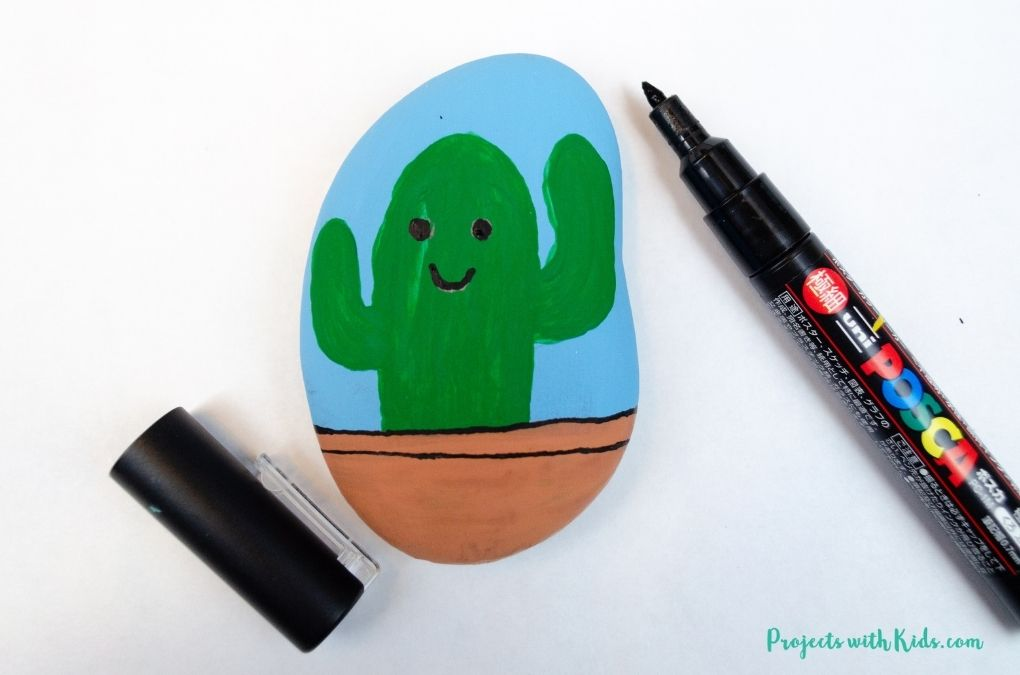 Drawing a face on a cactus with paint pens for a cactus painted rock art project