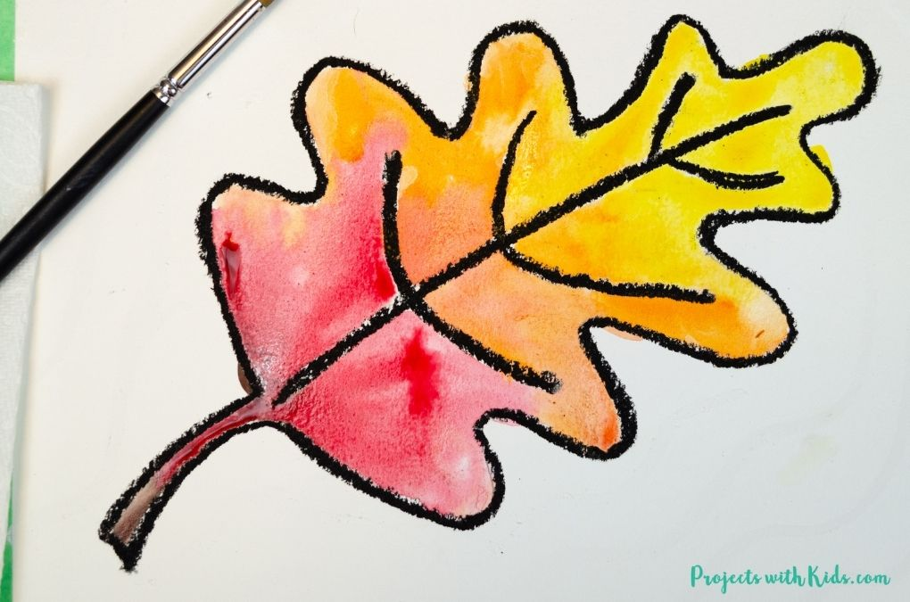 Painting fall colors on a leaf drawing with watercolor paint.