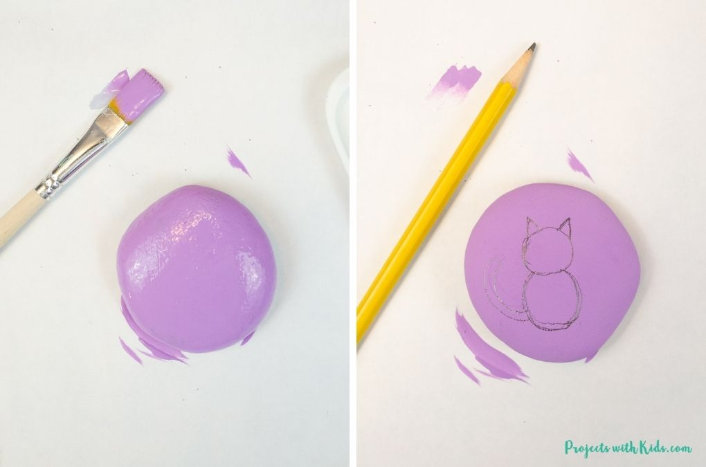 Painting a rock purple and drawing a simple black cat.