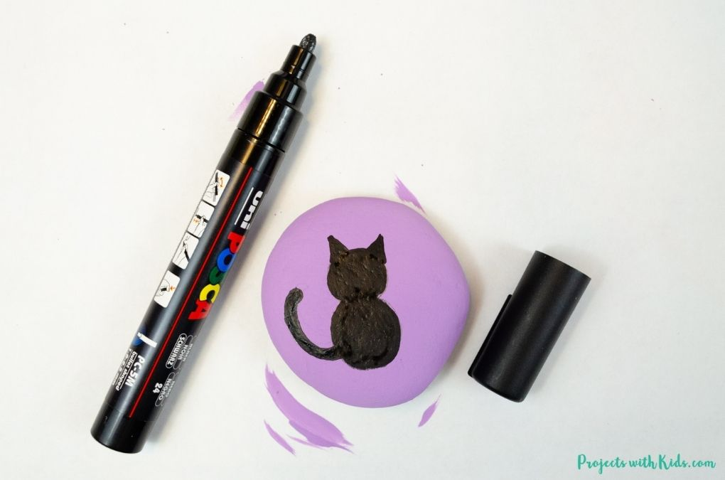 Coloring in a black cat on a painted rock with paint pens.