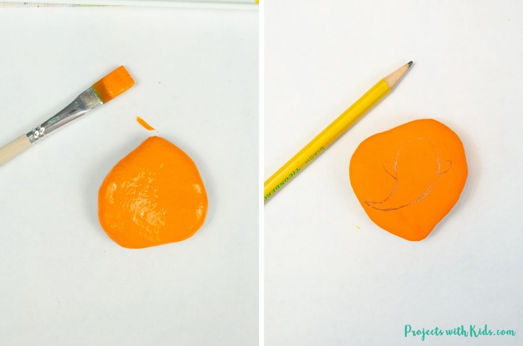 Painting a rock with orange paint and drawing a simple ghost on it.